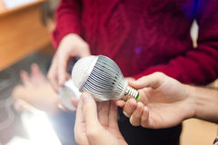 Bulb in hands. Presentation of a new bulb at an exhibition Stock Images