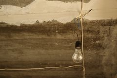 Bulb hanging on the wire from the grey concrete ceiling. Construction concept background royalty free stock image
