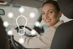 Bulb icon against woman driving photo Stock Photos
