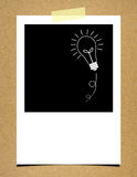 Bulb idea photo paper on board background Royalty Free Stock Image