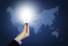 Bulb light in hand on world map stock images