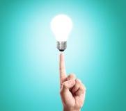 Bulb light on women fingertip. Hand Royalty Free Stock Photos