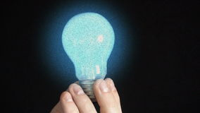 The bulb lights up in the hands of a young man, black background stock footage