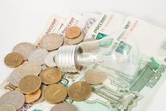 The bulb and is a lot of coins Royalty Free Stock Photo