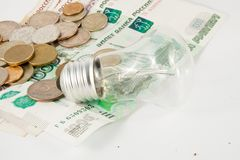 The bulb and is a lot of coins Royalty Free Stock Photography