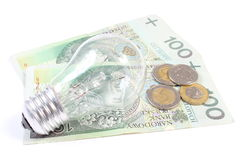 Bulb lying on heap of paper money. White background Stock Photography