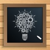 Bulb mechanism with cogs and gears written by chalk on blackboard Stock Photo