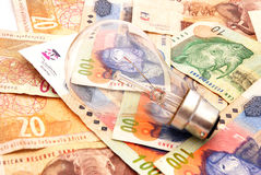 Electricity costs. A new light bulb on South African Rands money background Stock Photo