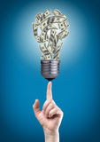 Bulb with money on tip of finger. Light bulb with money banknotes on tip of finger Stock Photo