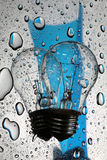 Bulb with reflection and drops on glass. Bulb on glass with drops of blue color royalty free stock image