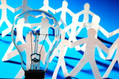 Bulb and team of paper man. Showing concept of teamwork Royalty Free Stock Photo