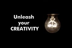 Bulb with text UNLEASH YOUR CREATIVITY. On black Royalty Free Stock Photo