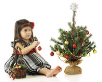 A Bulb for the Tree. An adorable preschooler preparing to place a red ornamant on her tiny Christmas tree.  On a white background Stock Photos