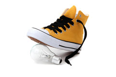 Bulb under sneaker Stock Images