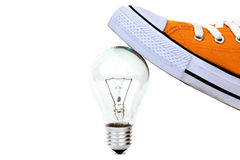 Bulb under yellow sneaker Royalty Free Stock Image