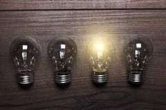 Bulb uniqueness concept on wooden background Royalty Free Stock Photos