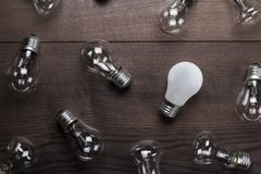Bulb uniqueness concept on the wooden table. Bulb uniqueness concept on brown wooden table Stock Photos