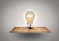 Bulb on wood shelf. A light royalty free stock images