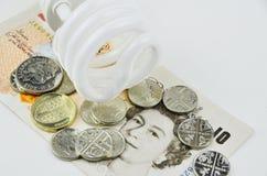 Bulbo ahorro de energía con el dinero Foto de archivo libre de regalías