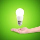 Bulbo ahorro de energía del LED que brilla intensamente en una mano Imagen de archivo libre de regalías