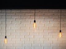 Bulbo bonde da iluminação velha, lâmpada retro em um fundo de uma parede de tijolo branca Bulbo de Edison que pendura em um fio T Foto de Stock Royalty Free