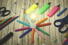 Bulbo brilhante com fontes de escola na tabela Fotografia de Stock