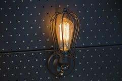 Bulbo de Edison da lâmpada do vintage, lâmpada de parede em um painel preto do metal fotografia de stock royalty free
