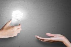 Bulbo de la idea, idea de la transferencia de mano a mano. Imagen de archivo libre de regalías