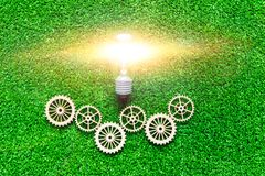 Bulbo de la luz eléctrica, engranajes en el fondo de la hierba verde artificial foto de archivo