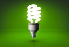 Bulbo de poupança de energia realístico no fundo verde no estúdio Imagem de Stock Royalty Free
