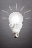 Bulbo del LED que brilla intensamente en fondo de la pizarra con los rayos Fotos de archivo