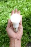 Bulbo do diodo emissor de luz - energia em nossa mão com iluminação fotografia de stock royalty free