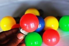 Bulbo e mão elétricos coloridos foto de stock