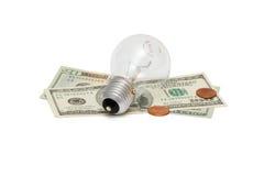 Bulbo eléctrico en cuentas de dólar con los centavos Imágenes de archivo libres de regalías