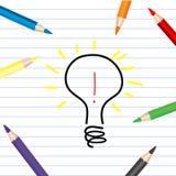 Bulbo estilizado que bosqueja en una hoja blanca con los lápices coloreados Foto de archivo