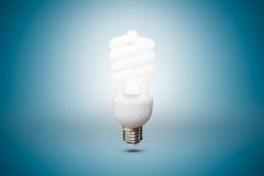 Bulbo fluorescente compacto no fundo azul Fotos de Stock