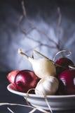 Bulbos da cebola vermelha e branca na placa na tabela preta Fotografia de Stock Royalty Free