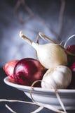 Bulbos da cebola vermelha e branca na placa na tabela preta Imagem de Stock
