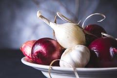 Bulbos da cebola vermelha e branca na placa na tabela preta Foto de Stock Royalty Free