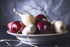 Bulbos da cebola vermelha e branca na placa na tabela preta Fotos de Stock