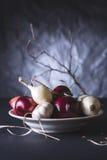 Bulbos da cebola vermelha e branca na placa na tabela preta Fotos de Stock Royalty Free