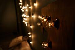 Bulbos de la luz eléctrica en una pared oscura Fotografía de archivo