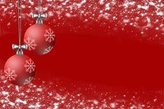 Bulbos de la Navidad exhibidos en un fondo rojo Nevado Foto de archivo
