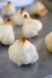 Bulbos del ajo asados en una cacerola de la asación Imágenes de archivo libres de regalías