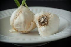 Bulbos del ajo en la placa de Whie Imagen de archivo libre de regalías
