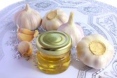 Bulbos del ajo y tarro de miel como la consumición sana Imagenes de archivo