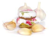 Bulbos del ajo y tarro de miel como la consumición sana Fotos de archivo