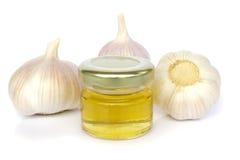 Bulbos del ajo y tarro de miel como la consumición sana Foto de archivo libre de regalías