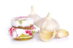 Bulbos del ajo y tarro de miel como la consumición sana Fotografía de archivo