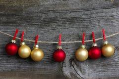 Bulbos del rojo y del oro de la decoración de la ejecución de la Feliz Navidad y Cl rojo Fotografía de archivo libre de regalías